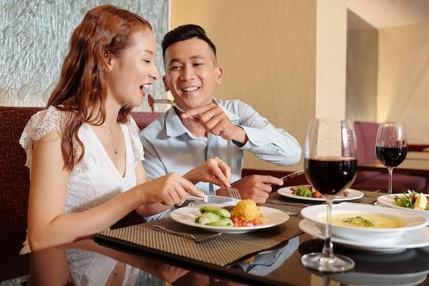 Gelukkig lachende jongeman die vriendin voedt met stuk vlees van zijn bord