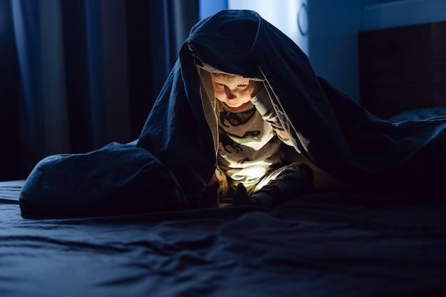 Gelukkig lachende jongen zittend in bed onder de dekens en spelen op de smartphone in het donker het gezicht van de baby wordt verlicht door een heldere monitor halloween slapeloosheid bij kinderen