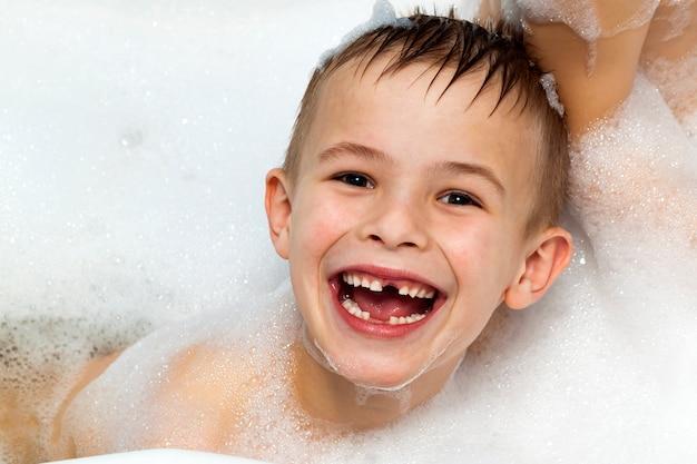 Gelukkig lachende kindjongen die een bad neemt.