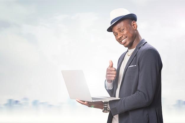 Gelukkig lachende knappe zakenman met laptopcomputer