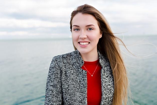 Gelukkig lachende langharige vrouw met grote blauwe ogen in rood shirt en grijze jas loopt in de buurt van de zee