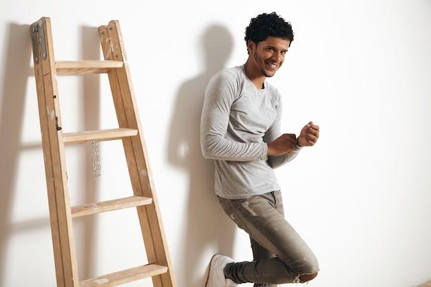 Gelukkig lachende latino donkere man draagt lege heide grijze kleding en poseren in de buurt van houten ladder op witte muur, zijaanzicht