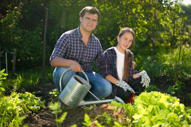 Gelukkig lachende man en schattig meisje aan het werk in de tuin met gieter