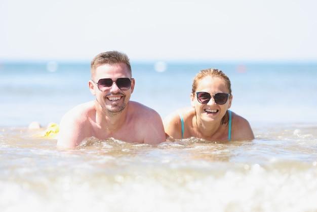 Gelukkig lachende man en vrouw in zonnebril liggen aan de kust