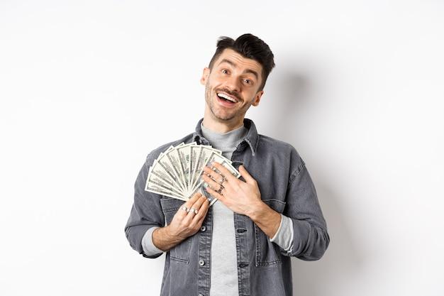 Gelukkig lachende man geld verdienen, dollarbiljetten knuffelen met blij opgelucht gezicht, staande tegen een witte achtergrond.