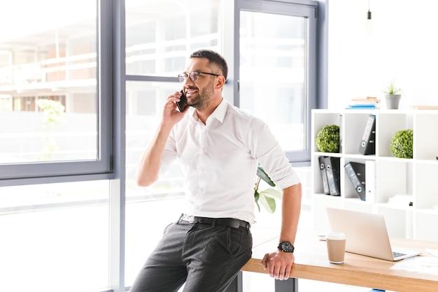 Gelukkig lachende man in formele kleding werken en spreken op zwarte smartphone, terwijl je in de buurt van groot raam in kantoor staat