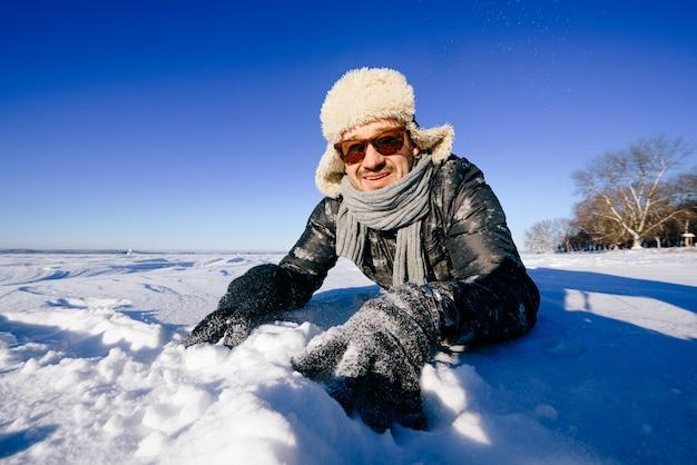 Gelukkig lachende man in zonnebril poseren in de sneeuw buitenshuis