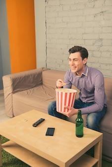Gelukkig lachende man kijken naar film met popcorn en bier