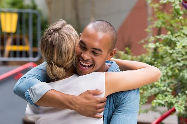 Gelukkig lachende man knuffelen jonge vrouw buiten café