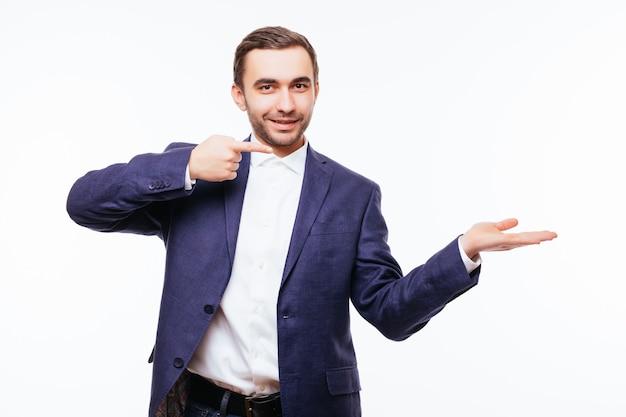 Gelukkig lachende man op shirt presenteren en iets laten zien op een witte muur