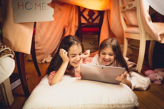 Gelukkig lachende meisjes met behulp van digitale tablet in huis gemaakt van dekens