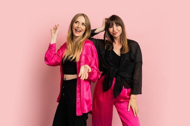 Gelukkig lachende modieuze meisjes dragen stijlvolle kleurrijke outfit, poseren op roze muur