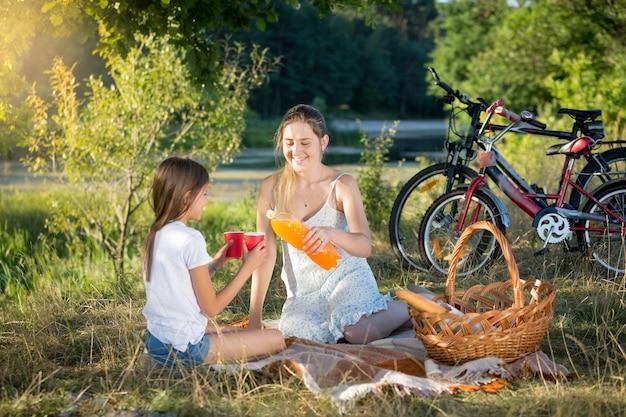 Gelukkig lachende moeder en dochter drinken sinaasappelsap bij picknick