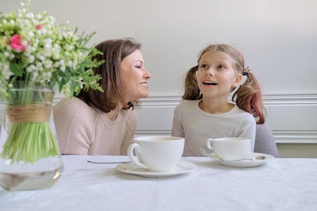 Gelukkig lachende moeder en dochtertje drinken aan tafel met cups