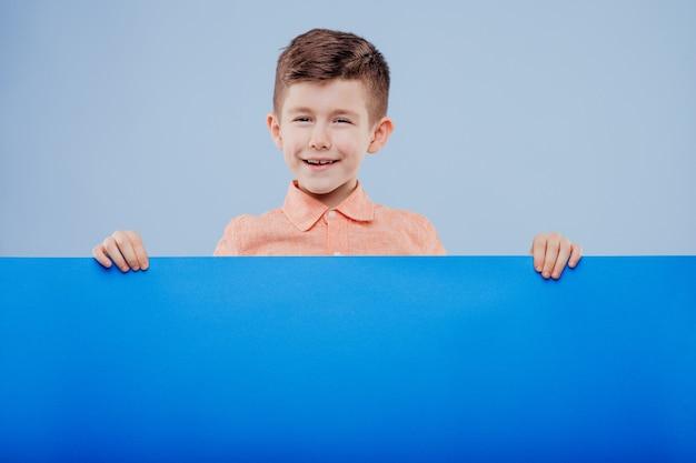 Gelukkig lachende mooie jongen met leeg bord of copyspace voor slogan of tekst, geïsoleerd op blauwe achtergrond, kopieer ruimte