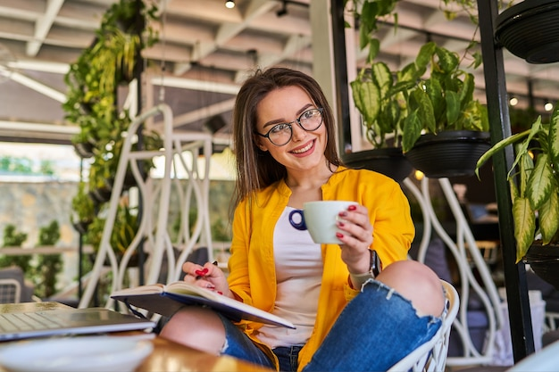 Gelukkig lachende mooie vrouw zitten en koffie drinken.