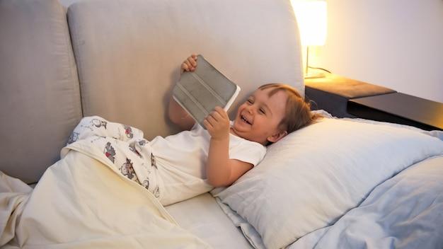 Gelukkig lachende peuterjongen die 's nachts in bed ligt en tekenfilms kijkt op digitale tabletcomputer.