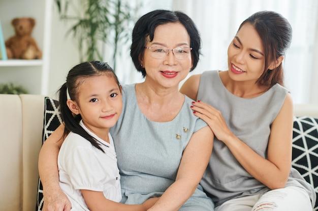 Gelukkig lachende senior vrouw die geniet van tijd doorbrengen met haar volwassen dochter en preteen kleindochter thuis in het weekend