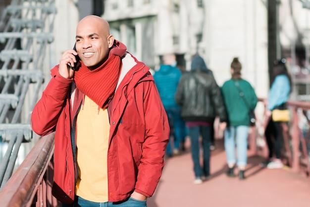 Gelukkig lachende spaanse kale man van middelbare leeftijd die op straat aan de telefoon praat