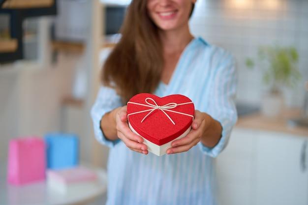 Gelukkig lachende tevreden schattige geliefde vrouw houdt een hartvormige geschenkdoos vast voor valentijnsdag voor 14 februari