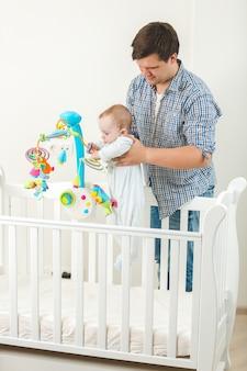 Gelukkig lachende vader houdt zijn schattige baby in bedje op kinderdagverblijf