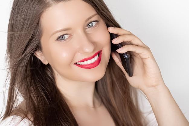 Gelukkig lachende vrouw bellen op smartphone portret op witte achtergrond mensen technologie en communicatie concept