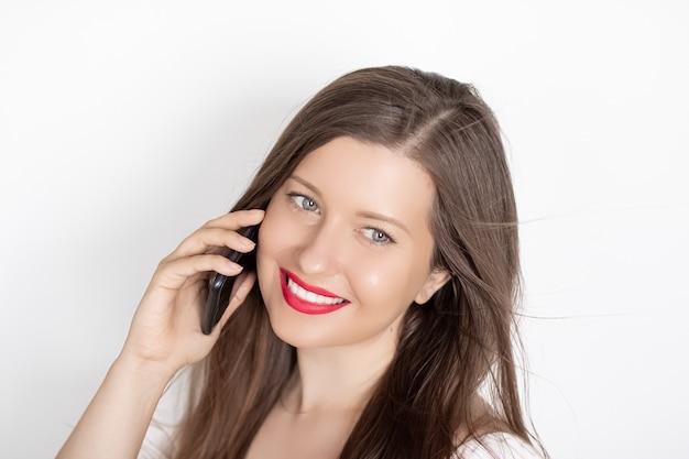 Gelukkig lachende vrouw bellen op smartphone portret op witte oppervlakte mensen technologie en communicatie concept