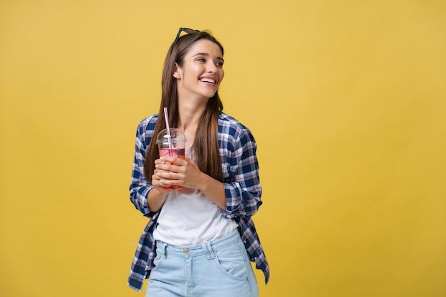 Gelukkig lachende vrouw die een casual doek draagt en een tropische cocktail drinkt, geïsoleerd op een gele achtergrond.
