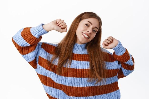Gelukkig lachende vrouw die haar handen uitstrekt, dansen en plezier hebben op vrije tijd, ontspannen en zorgeloos kijken, witte muur