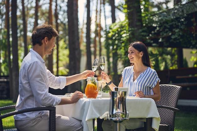 Gelukkig lachende vrouw en man ontspannen in het diner in de groene tuin
