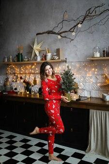 Gelukkig lachende vrouw in rode kerst pyjama's met plezier in de donkere keuken versierd met slingers