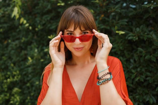 Gelukkig lachende vrouw in stijlvolle rode zonnebril en oranje jurk poseren buiten over tropische tuin.