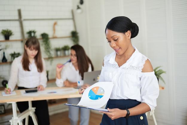 Gelukkig lachende vrouw kijkt naar grafieken en werkdocumenten op kantoor tegen de achtergrond van het vrouwelijke team.