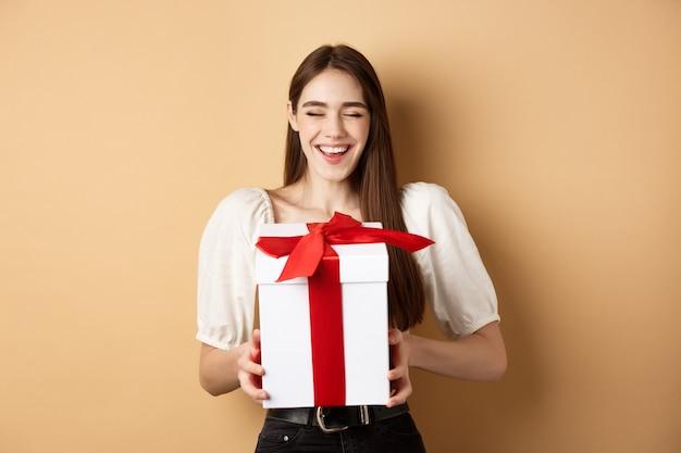 Gelukkig lachende vrouw lachen, geschenkdoos van minnaar te houden, genieten van romantische date op valentijnsdag
