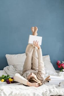 Gelukkig lachende vrouw liggend op het bed in pyjama, met plezier genieten van bloemen en het lezen van een boek