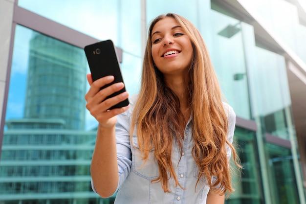 Gelukkig lachende vrouw lopen in de zakenwijk met behulp van een smartphone.