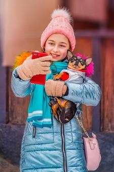 Gelukkig lachende vrouw maakt zelfportret op smartphone in winterdag. tienermeisje en chihuahua.