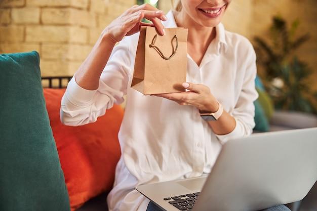 Gelukkig lachende vrouw met cadeau in handen