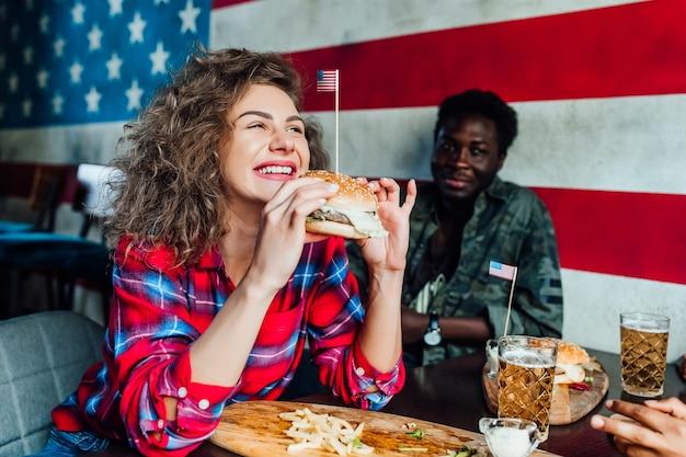 Gelukkig lachende vrouw met een rust in de bar met man in café, praten, lachen eten fast food.