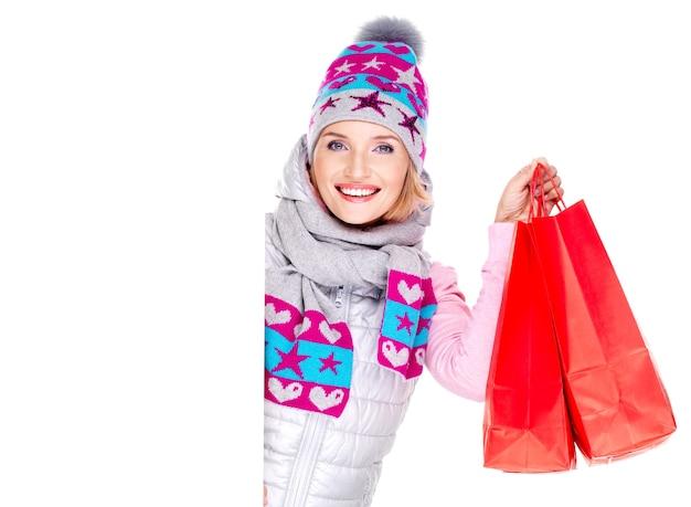 Gelukkig lachende vrouw met geschenken na het winkelen kijkt uit van het witte lege bordje