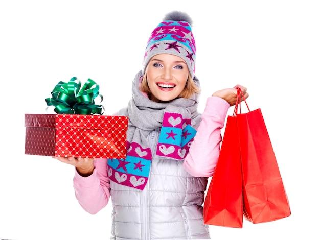 Gelukkig lachende vrouw met geschenken na het winkelen op wit wordt geïsoleerd