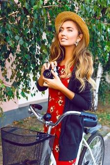 Gelukkig lachende vrouw met plezier en verrast speelse emoties, alleen wandelen met stijlvolle retro fiets in stadspark, rode jurk warme trui en vintage strooien hoed dragen, hebben lange blonde haren gekruld.