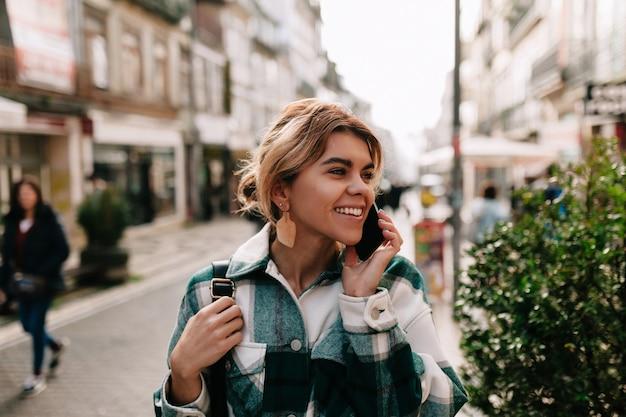 Gelukkig lachende vrouw met verzamelde blond haar praten over smartphone op straat