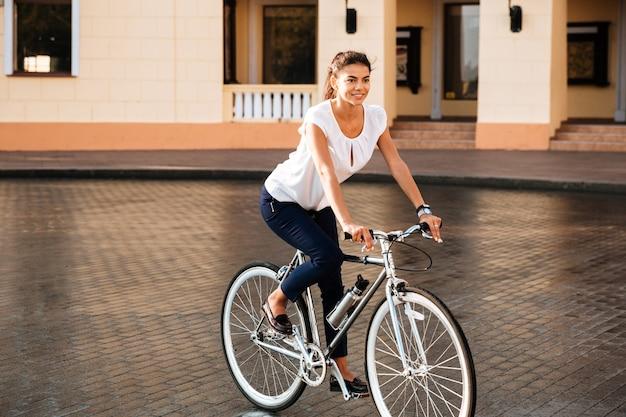 Gelukkig lachende vrouw op de fiets op de straat in de stad