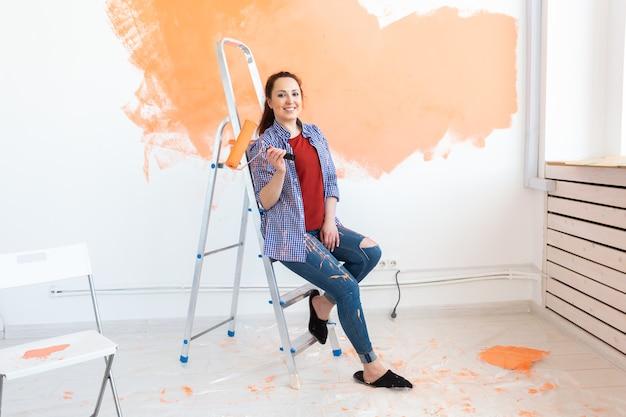 Gelukkig lachende vrouw schilderij binnenmuur van nieuw huis. herinrichting, renovatie, reparatie van appartementen