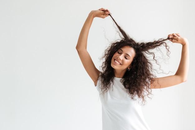 Gelukkig lachende vrouw speelt met haar lang krullend haar