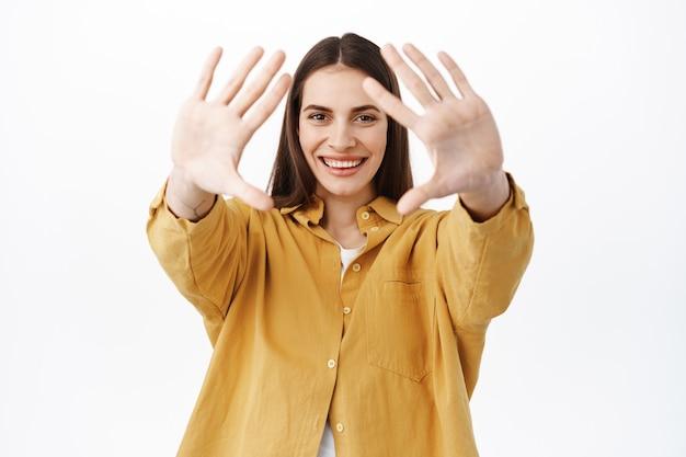 Gelukkig lachende vrouw strekt de handen naar voren en kijkt door dromerig, iets moois voorstellend, een interessant concept creërend, staande over een witte muur