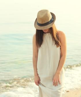 Gelukkig lachende vrouw wandelen op een zee strand gekleed in witte jurk en hoed die betrekking hebben op gezicht, ontspannen en genieten van frisse lucht.