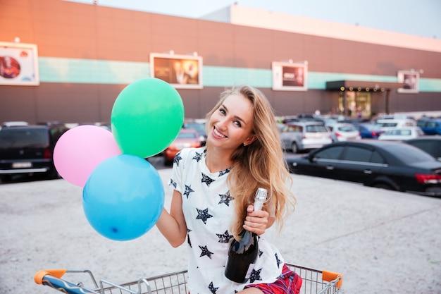 Gelukkig lachende vrouw zitten in winkelwagen met ballonnen en fles champagne