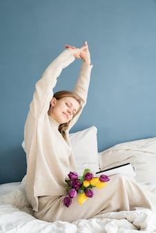 Gelukkig lachende vrouw zittend op het bed in pyjama, met plezier genieten van bloemen en het lezen van een boek